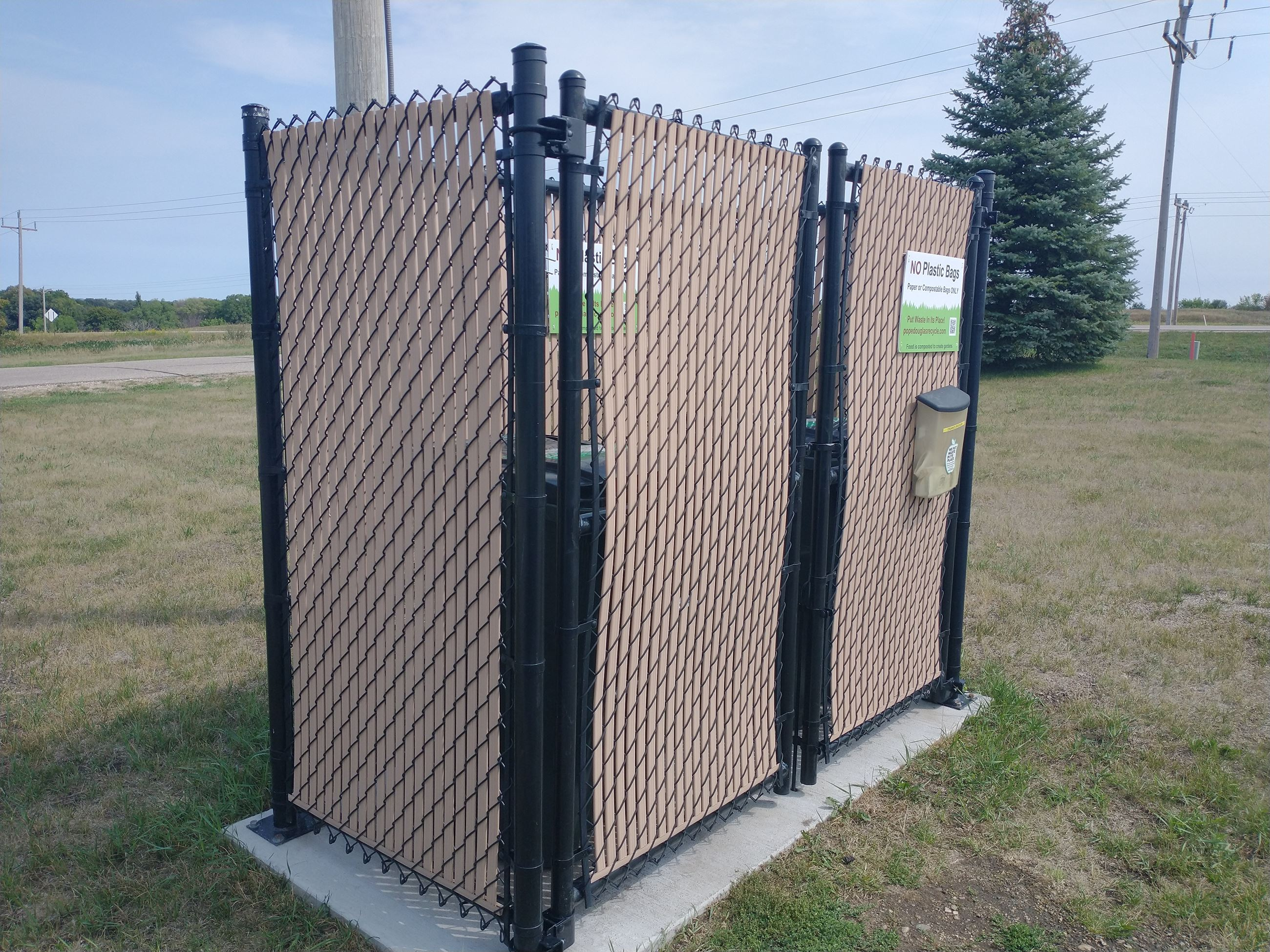 A tall brown fence structure sits on a concrete slab, inside the fence gate are two organics carts.