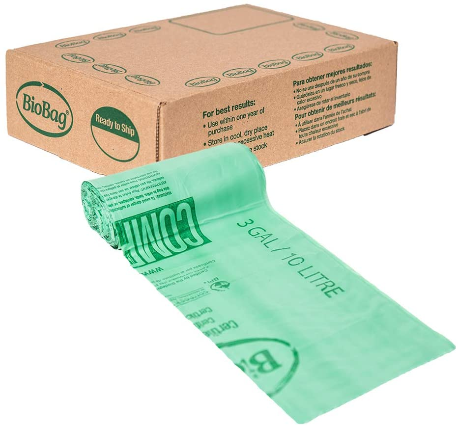 A roll of green 3 gallon bags sits in front of the brown box they come in.